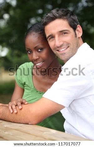 An interracial couple in a park. - stock photo