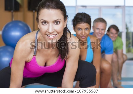 An interracial group of middle aged people, men and women, practicing yoga at a gym - stock photo