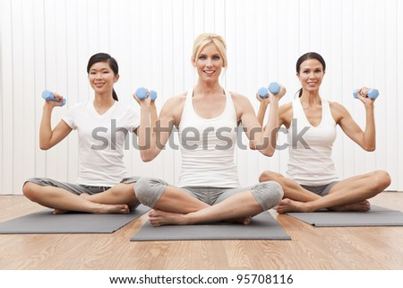 An interracial group of three beautiful young women sitting cross legged in a yoga position at a gym and weight training - stock photo