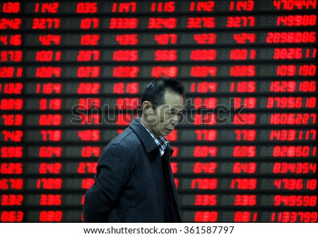 An investor watches electric board in a stock market in Huaibei, Anhui province, east China on 9th November 2015.  - stock photo