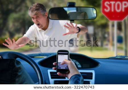 An irresponsible texting driver is about to run over a pedestrian at an intersection which shows how dangerous texting and driving is. Stop the text and stop the wrecks. - stock photo