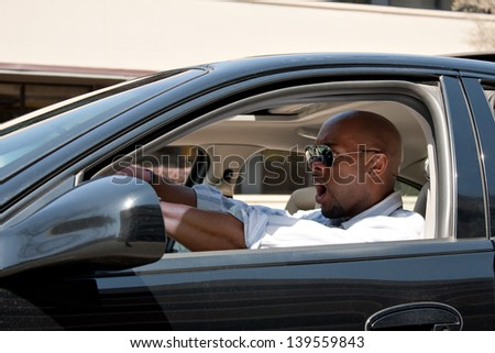 An irritated business man driving a car is expressing his road rage and anger. - stock photo