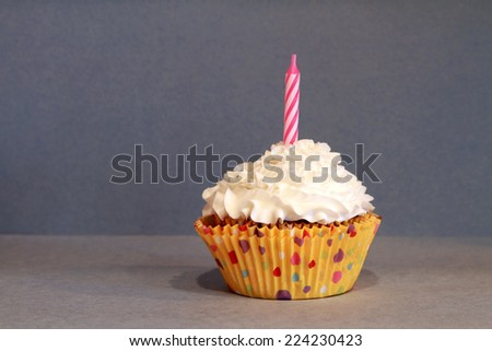 An isolated chocolate cupcake with vanilla frosting on a blue background and a candle. - stock photo