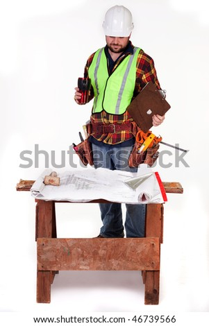 an isolated construction worker looking at blueprints - stock photo