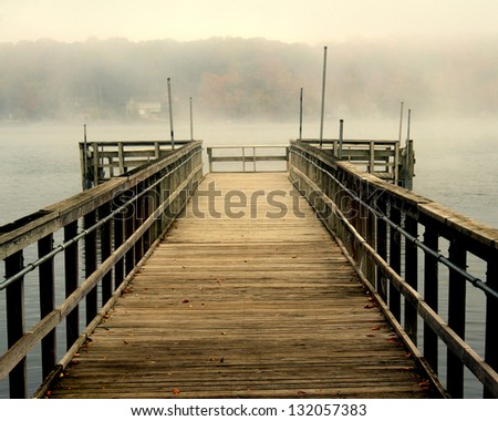 An isolated fishing pier on a misty morning in Wisconsin - stock photo