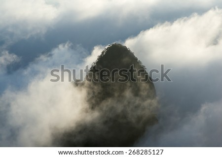 An isolated granite mountain peak in a sea of clouds during the blue hour of sunrise, Huangshan (Yellow Mountains), Anhui Province, China - stock photo