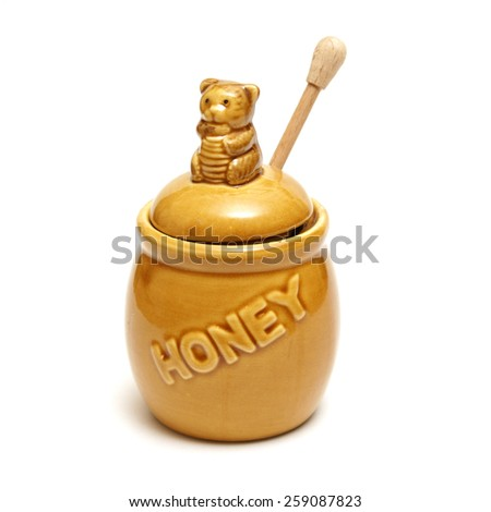 An isolated shot of a honey pot and dipper. - stock photo