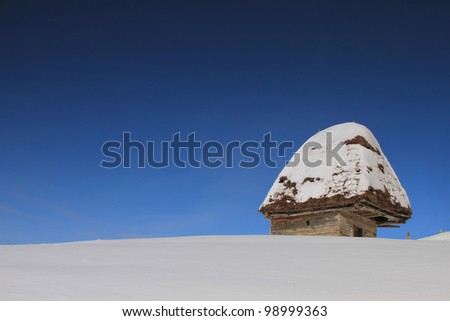 An isolated vintage house in a winter landscape - stock photo