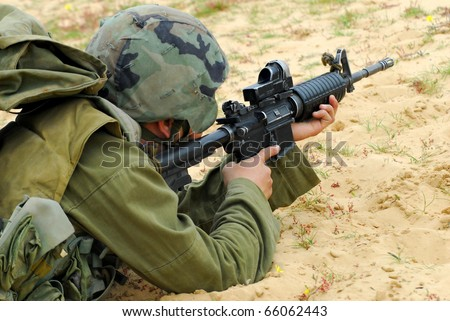 An Israeli defense forces soldier dressed in uniform aims his M16 rifle while on duty. Concept photo of war ,military, army, armed forces, incursion,conflict ,firearm ,battle, attack.   - stock photo