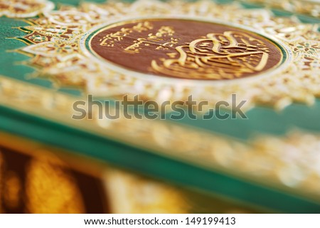 An macro image of the Quran. The Quran literally meaning 'the recitation' is the central religious text of Islam, which Muslims believe to be the verbatim word of God or Allah - stock photo