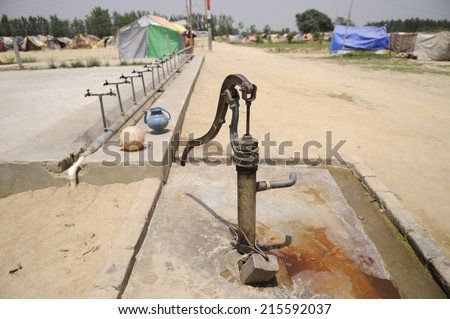An Mark II handpump in front of a tent city in India. - stock photo