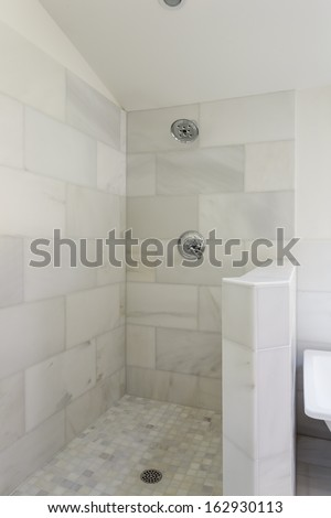 An modern, marble-tiled, open-aired walk-in shower with shower head, fixture, and drain.  - stock photo
