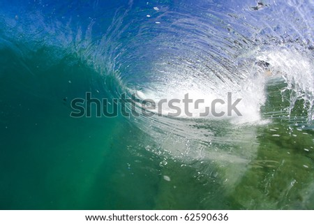 An ocean tube breaks in crystal clear water. - stock photo