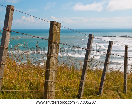 An oceanview behind a batten sheep fence on a cape - stock photo