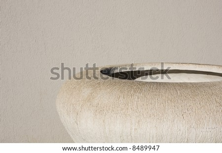 An off-white cement planter stands empty in front of a cement wall. - stock photo