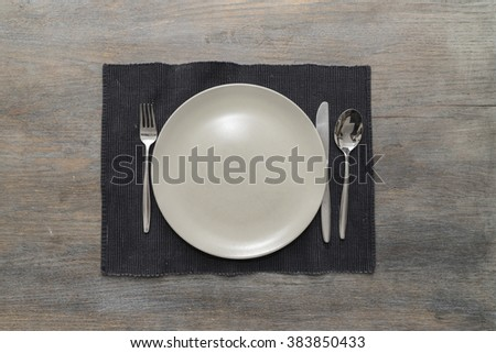 An off-white plate with fork, knife and spoon on a black placemat on a wooden table - stock photo