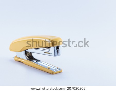 an office stapler with yellow hand grip isolated on white background - stock photo