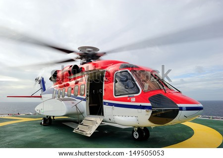 An offshore helicopter is waiting for passengers on the helideck - stock photo