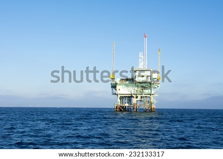 An offshore oil platform rests in deep ocean water on a clear, bright, sunny day.  - stock photo