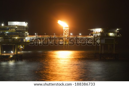 An offshore oil platform with a flare tower at night - stock photo