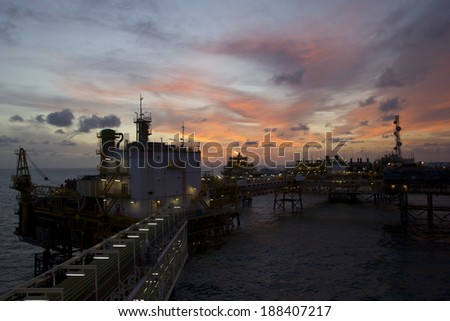 An offshore oil -rig during sunset - stock photo