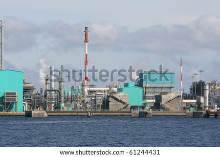 An oil refinery on the coast.  This industrial looking building is located near a port.  There is some gas being released. - stock photo