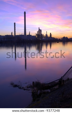 An oil refinery, situated in a commercial harbor, during a radiant sunset. HDR  image - stock photo