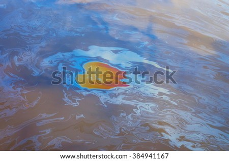 an oil slick on the water surface - stock photo