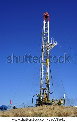 An oil well servicing rig sets up in Kern County California - stock photo