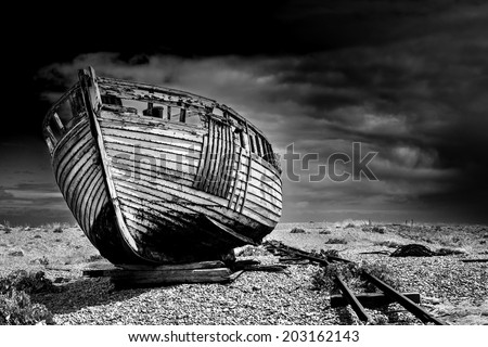 An old abandoned fishing boat stranded on a beech in black and white. - stock photo
