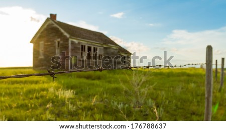An old abandoned one room school house on the prairies - stock photo