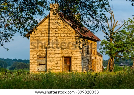 An Old Abandoned Texas Homestead Farmhouse in a Beautiful Field Full of Various Texas Wildflowers. - stock photo