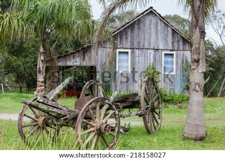An old abandoned wagon with wooden houses in the background - stock photo