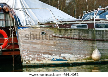 an old aged wooden boat with peeling, cracked and chipped blue paint on the hull, moored to a pontoon on the river waiting to be restored, scrapped or bought - stock photo