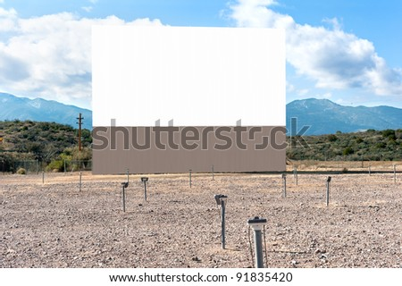 An old and functional drive in theater with blank projection screen in a dessert setting and window speakers on posts for sound. - stock photo