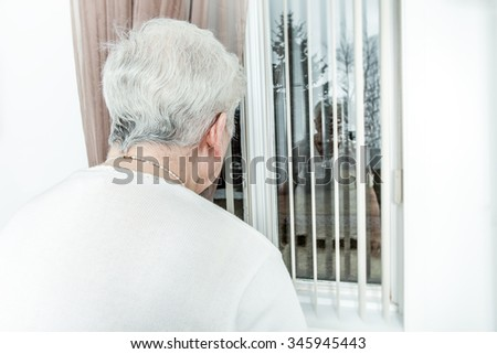 An Old and lonely lady looking outside through her window - stock photo