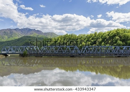 An old and new bridge crossing a big river with mountains in background - stock photo