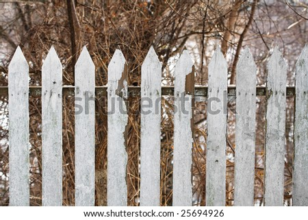 An old and white picket fence. - stock photo