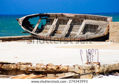 An old and wrecked wood boat, on a roof near the sea - stock photo