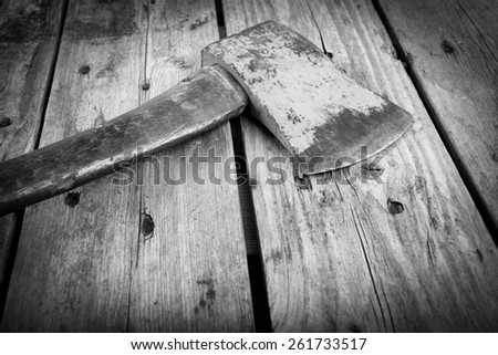 An old axe with a wooden handle and wear marks sits on a rough timber background in black and white - stock photo