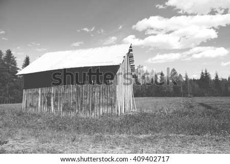 An old barn in the green field in Finland. Image taken on a sunny day and some clouds are in the sky. Image in black and white. - stock photo