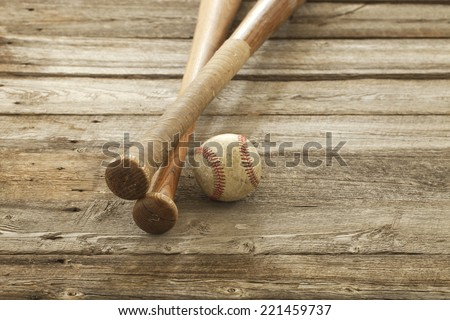 An old baseball and wooden bats on a rough wood surface - stock photo