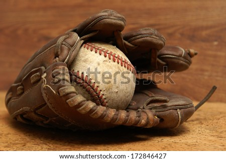 An old baseball inside a well used glove. - stock photo