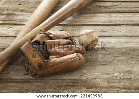 An old baseball, mitt and wooden bats on a rough wood surface - stock photo