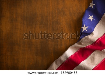 An old Betsy Ross Flag, with dingy white stripes and stars, on worn rustic wood. - stock photo