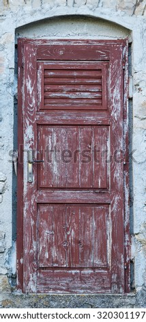 an old brown yellow ragged shabby wooden door - stock photo