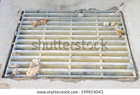 An old cast iron storm drain for storm water runoff in the ground. - stock photo