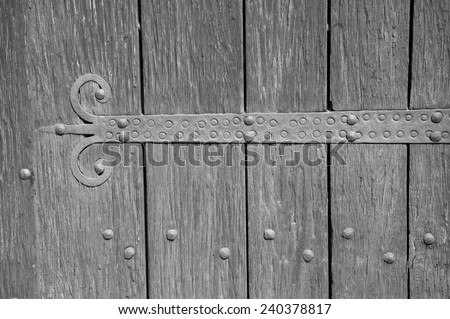 An old castle gate with rusty door hinge. Aged photo. Black and white. - stock photo