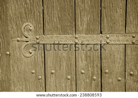 An old castle gate with rusty door hinge. Aged photo. Sepia. - stock photo