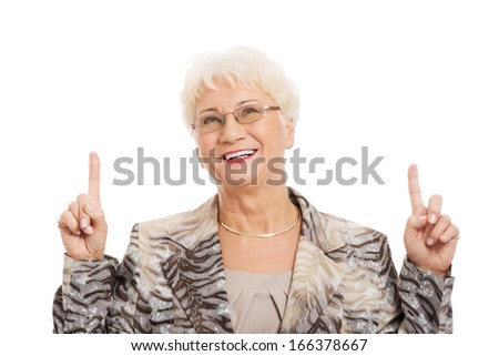 An old casual lady pointing up on copy space. Isolated on white.  - stock photo